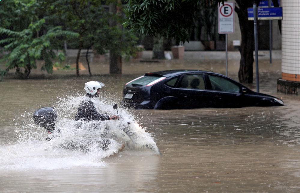 Motociclista anda por rua alagada em decorrência de fortes chuvas no Rio de Janeiro