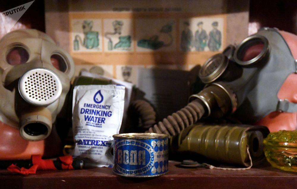 Ao fundo, cartaz de instruções, com lata e saquinho de água da época soviética, que deveria ser tomada em caso de carência de recurso, rodeados de máscaras