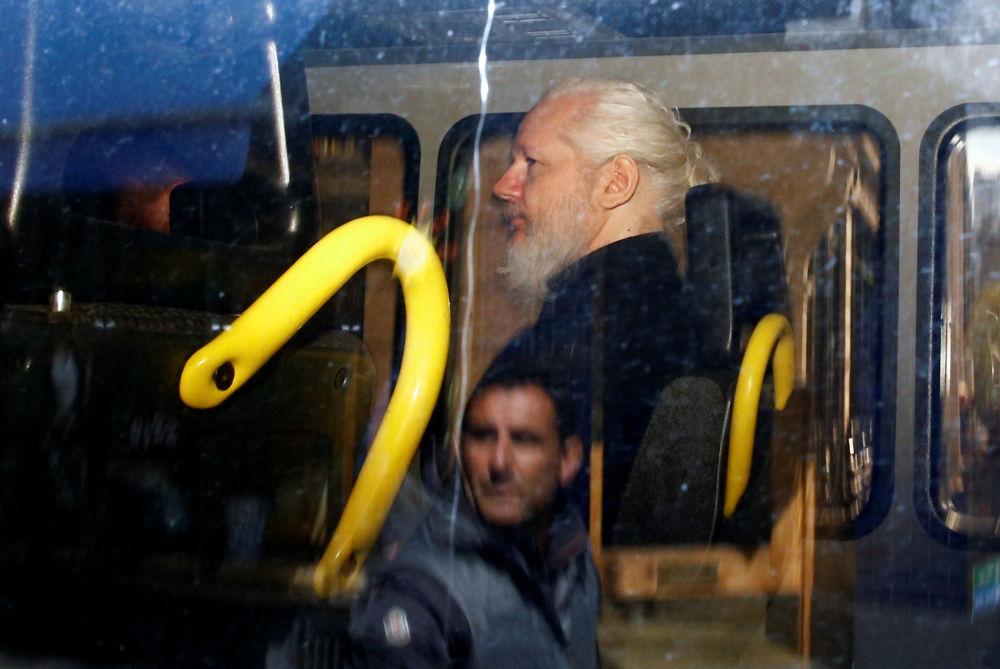 Reflexo de um homem na janela do carro de polícia com o fundador da WikiLeaks
