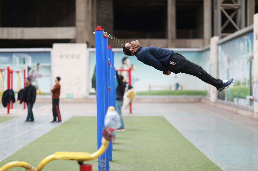 Homem faz exercícios com equipamento improvisado na China