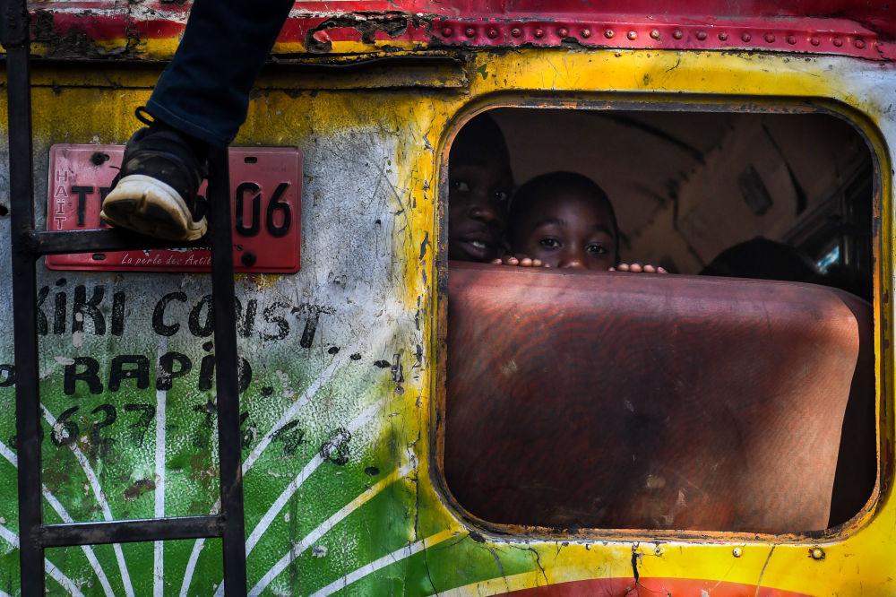 Garotos dentro de ônibus no Haiti