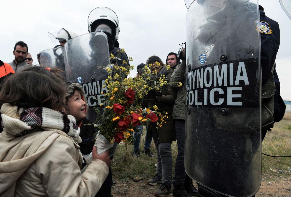 Crianças distribuem flores a policiais gregos após confrontos