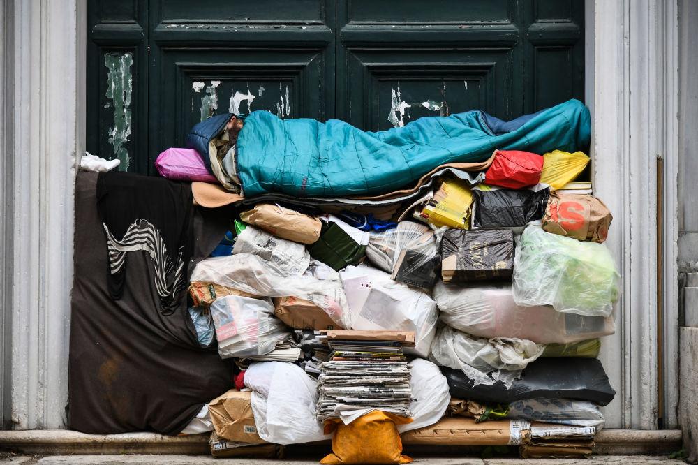 Desabrigado dorme em pilha de plástico e jornais na Itália