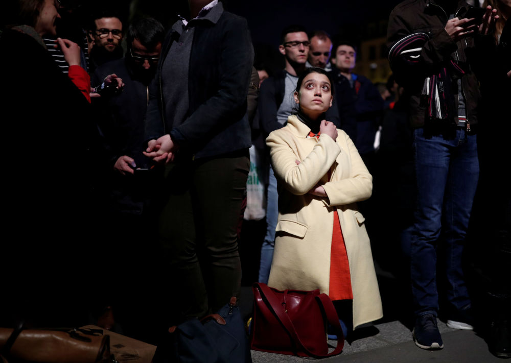 Pessoas observam o incêndio na Catedral de Notre-Dame