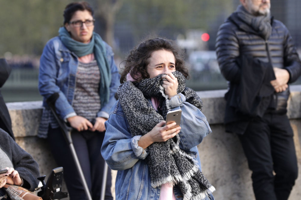 Uma menina chora ao ver incêndio na Catedral de Notre-Dame