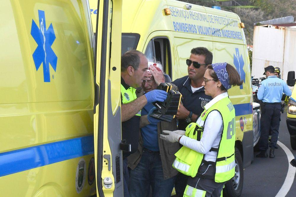 Homem recebendo assistência médica após o acidente com ônibus na Madeira