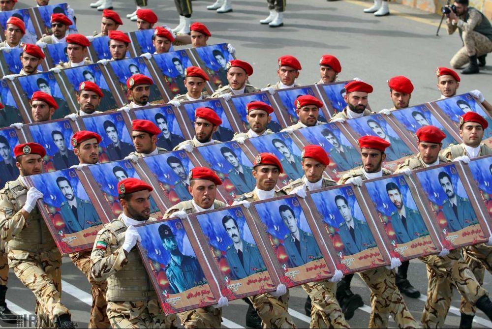 Representantes do Corpo de Guardiões da Revolução Islâmica (CGRI) desfilam com retratos de heróis mortos nas guerras passadas