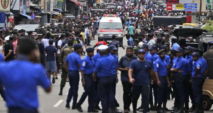 Ambulância tenta passar por multidão para prestar assistência às vítimas do atentado em Colombo, capital do Sri Lanka