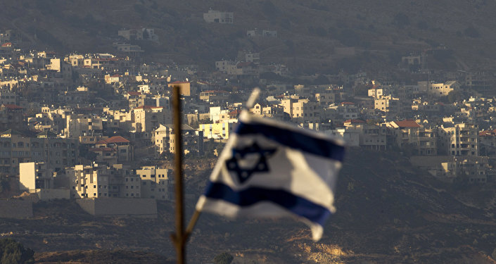 Uma bandeira israelense em frente à aldeia de Majdal Shams nas colinas de Golã controladas por Israel.