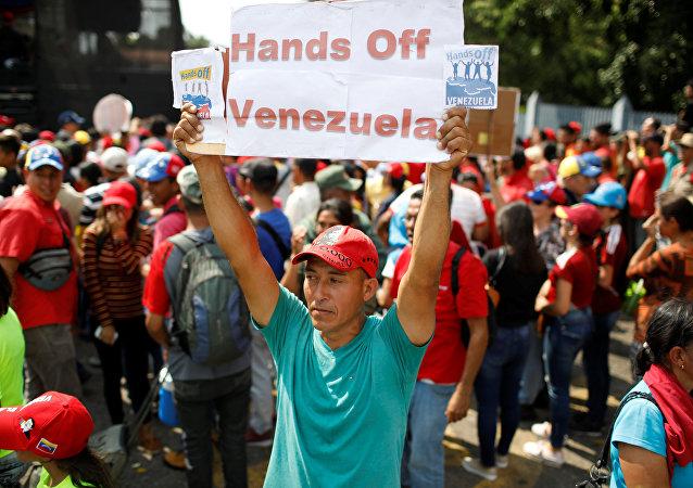 Un partidario de Nicolás Maduro con la pancarta Manos fuera de Venezuela