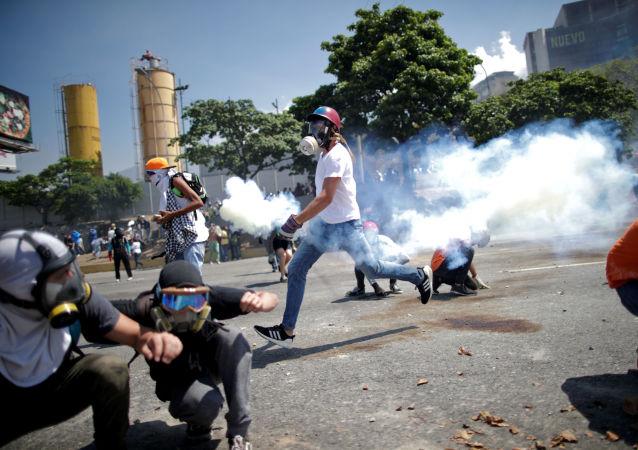 Opositores a Maduro se esquivam de gás lacrimogêneo perto da base aérea La Carlota, em Caracas