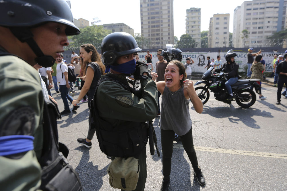 Jovem grita com soldado rebelde perto da base aérea La Carlota, em Caracas