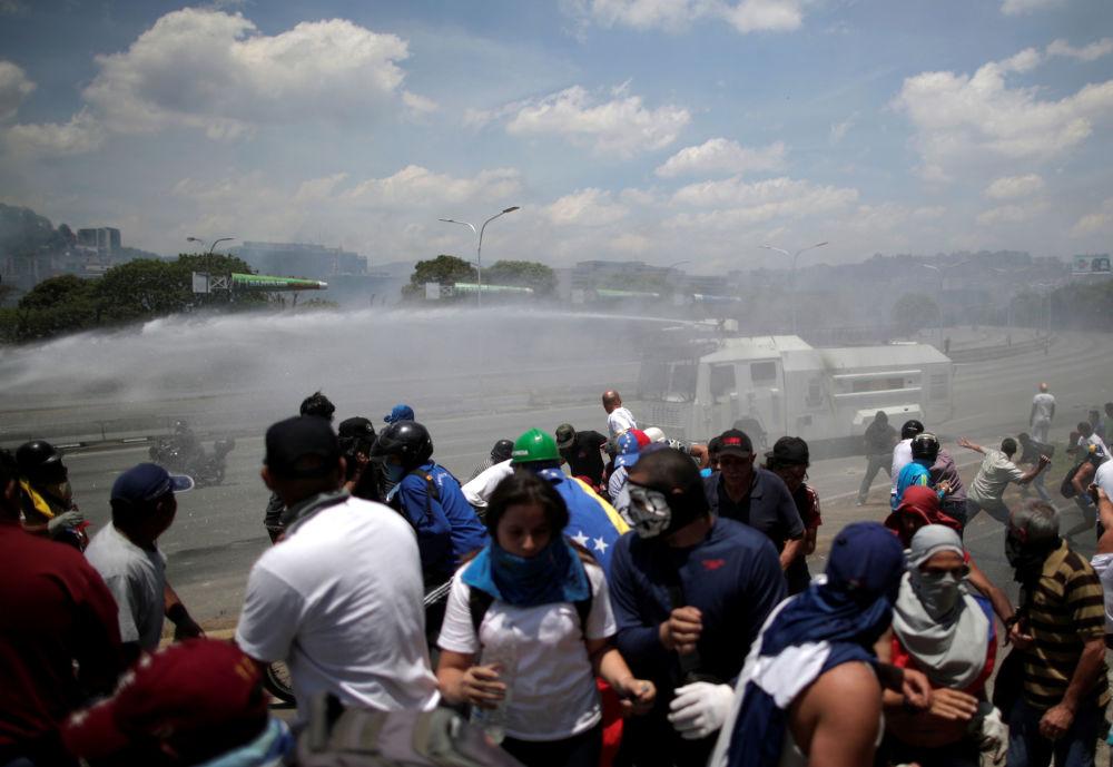 Veículo blindado jorra jatos de água para dispersar manifestantes opositores ao governo de Maduro perto da base aérea La Carlota, em Caracas