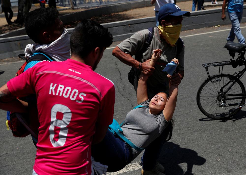 Pessoas carregam jovem ferida durante protestos perto da base aérea La Carlota, em Caracas