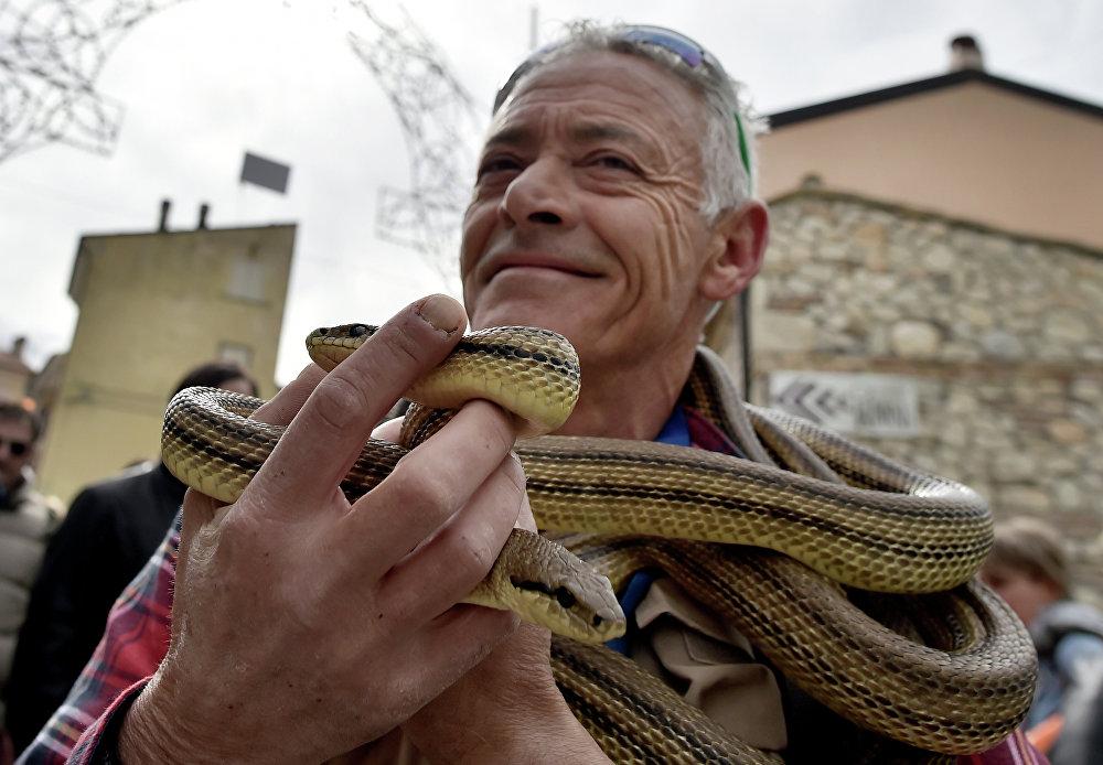Homem segurando uma cobra no decorrer da procissão anual nas ruas da vila italiana de Cocullo