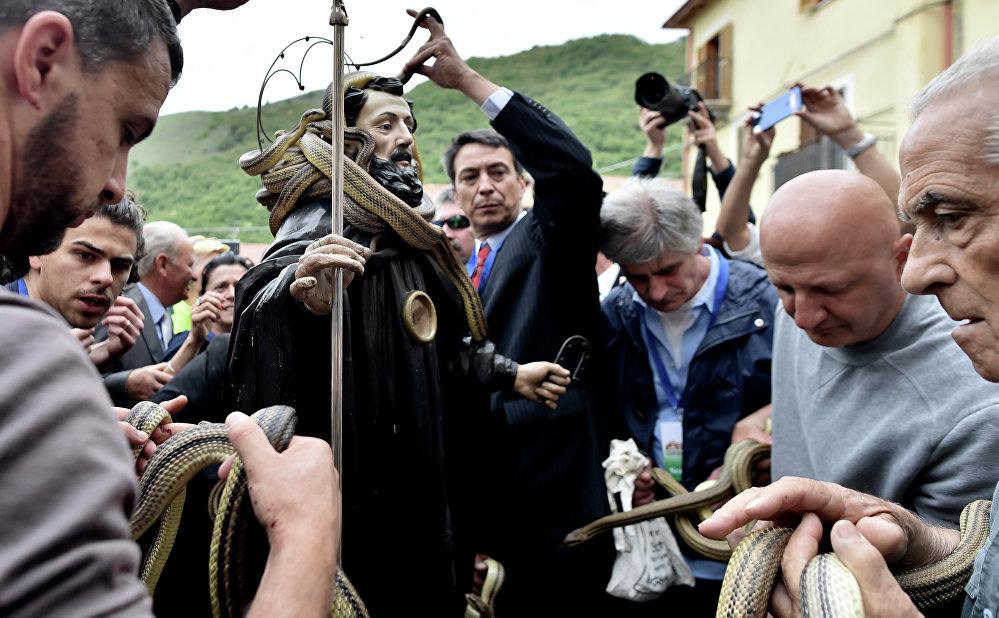 Pessoas retirando suas cobras da estátua de São Domingos de Gusmão durante a celebração do festival anual dos Serpari nas ruas da vila italiana de Cocullo