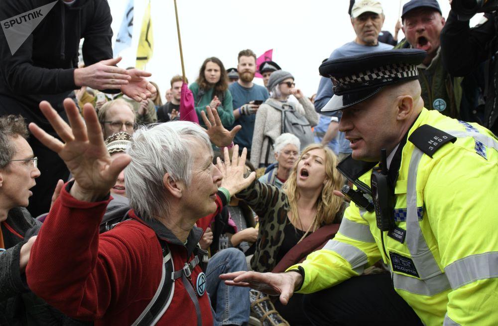 Policial fala com uma ativista do grupo ambientalista Extinction Rebellion durante protestos em Londres