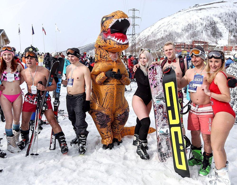 Participantes posam para foto ao lado de uma pessoa fantasiada de dinossauro no festival Khibiny-Bikini 2019, na cidade de Kirovsk, Rússia