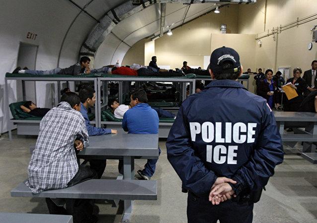 Um oficial da Imigração e Fiscalização Aduaneira (ICE) observa um grupo de 116 imigrantes salvadorenhos que esperam ser deportados, na instalação de detenção em Raymondville, Texas.