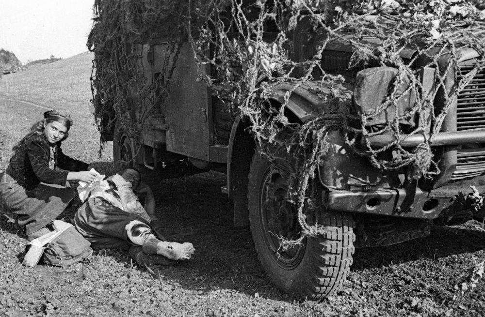 Menina romena faz curativo em um soldado soviético, 1944
