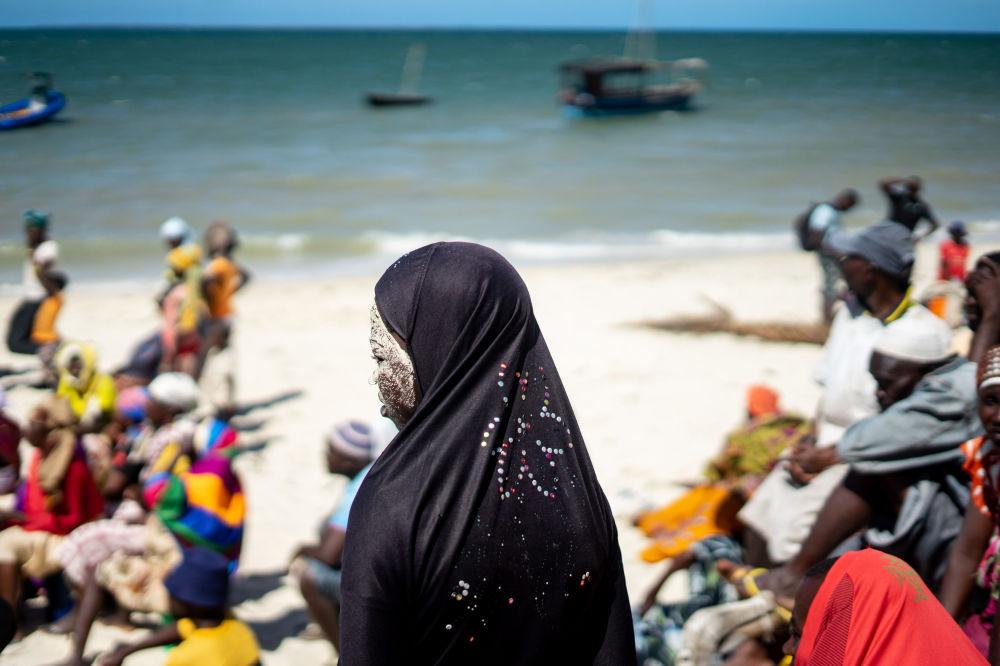 Man Yam, de 19 anos, na praia à espera de receber ajuda depois de um ciclone devastador na aldeia de Kumwamba, Moçambique