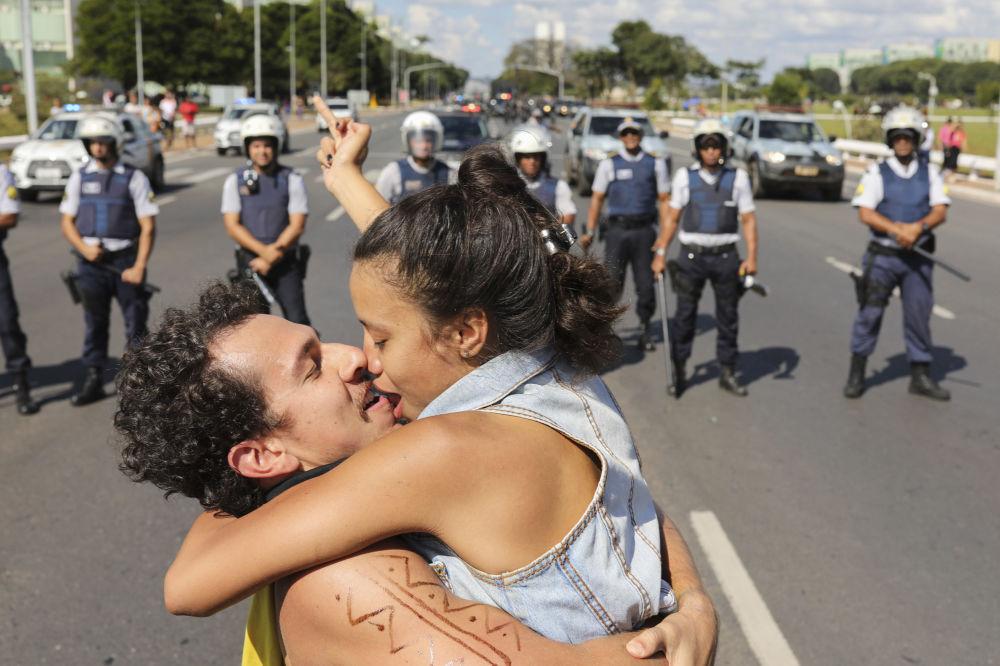 Um casal se beijando na frente da polícia durante protestos no Brasil
