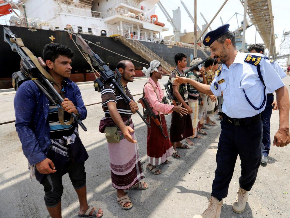 Oficial da Guarda Costeira iemenita cumprimenta hussitas quando estes deixam o porto de Saleef, na província de Hodeyda