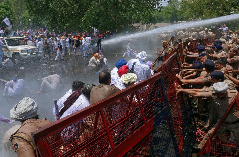Manifestantes atingidos por jatos de água da polícia durante um protesto em Chandigarh, na Índia