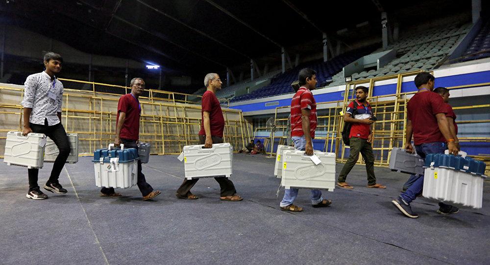 Membros da equipe eleitoral carregam máquinas de votação eletrônica após coletá-las de um centro de distribuição durante a sétima e última fase da eleição geral indiana.