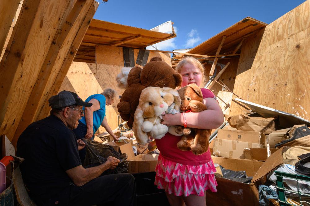 Menina junta seus ursinhos de pelúcia após sua casa ser atingida por tornado em Jefferson City, capital do estado norte-americano de Missouri