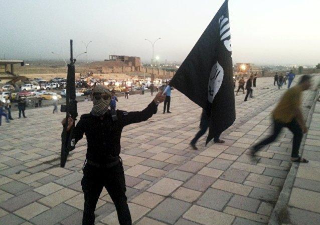 Um combatente do Daesh segura uma bandeira do grupo terrorista e uma arma na cidade de Mosul, no Iraque.
