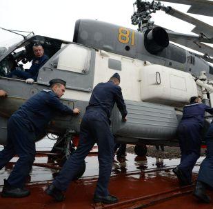 Fuzileiros russos preparam para o voo um helicóptero Ka-27 durante as manobras de busca e salvamento realizadas com participação da Frota do Pacífico e da Força Marítima de Autodefesa do Japão SAREX 2019.