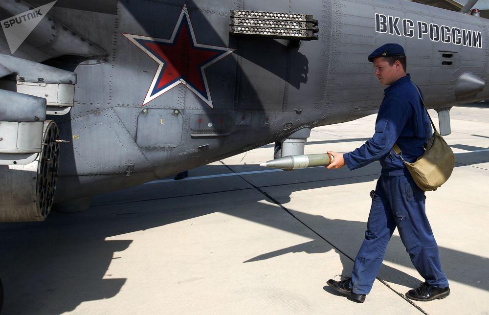 Militar municia um helicóptero de ataque Mi-35 durante manobras aéreas da aviação tático-operacional