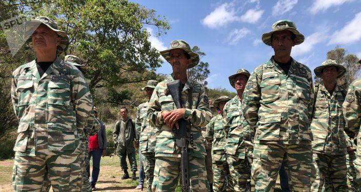 Oficiais das milícias prestam apoio para treinar a população civil a se preparar em caso de guerra