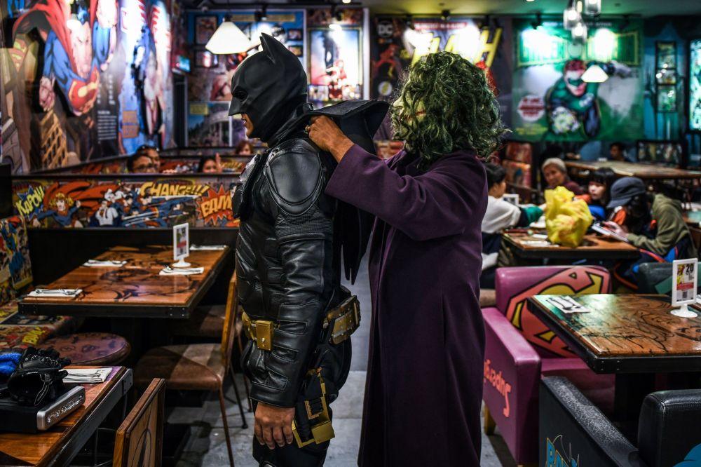 Cosplayers usando trajes de Batman e Coringa para a comemoração do 80º aniversário do Batman, na Malásia