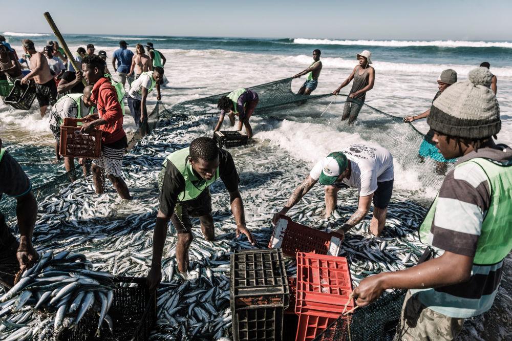 Moradores locais pescam com redes em praia de Amanzimtoti, na África do Sul