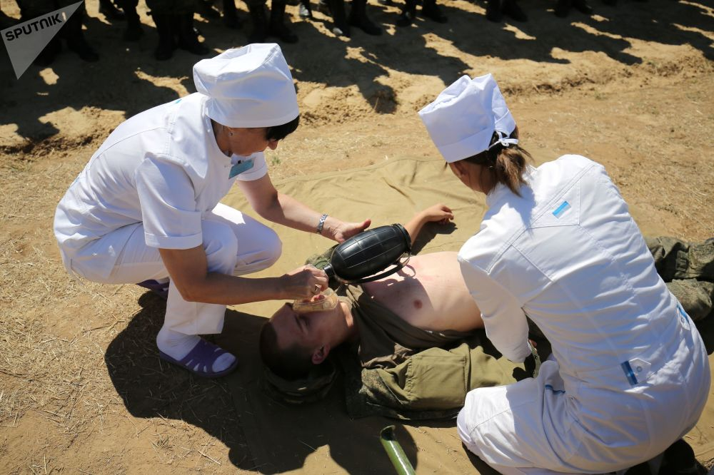 Duas enfermeiras treinam prestação de primeiros-socorros, em exercício de simulação no polígono militar Prudboi, no Distrito Militar Sul, região de Volgogrado