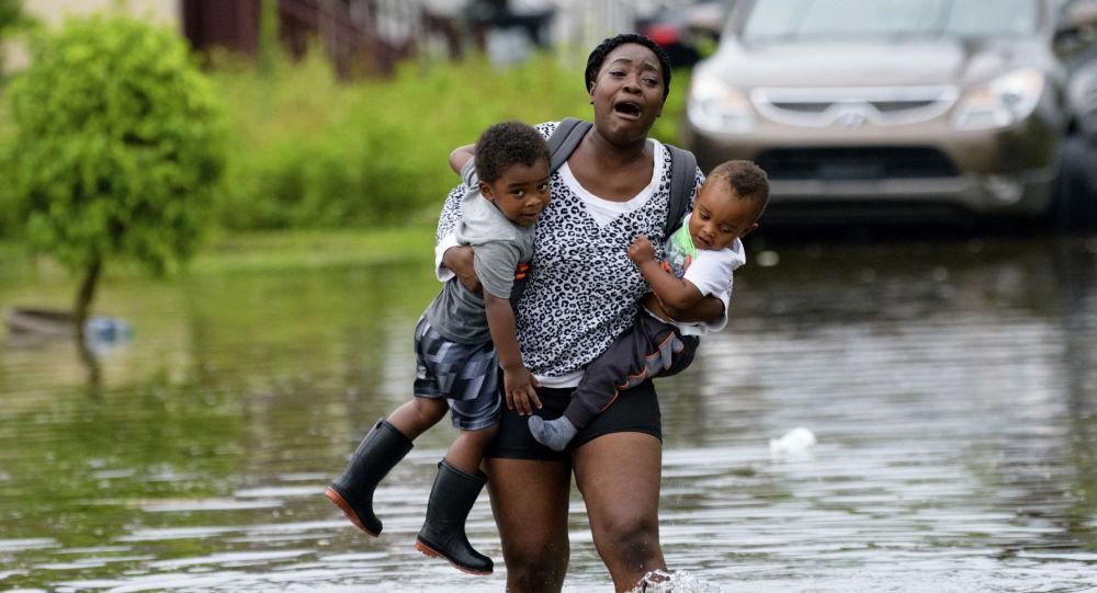 Mãe carregando seus filhos durante a inundação em Nova Orleans (EUA)