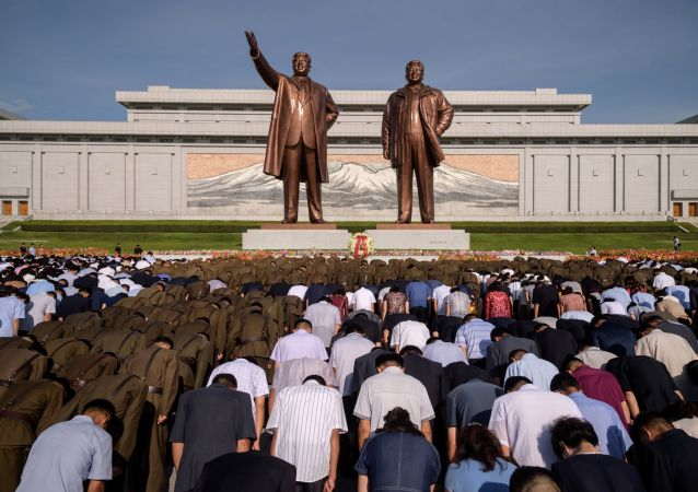 Moradores da cidade de Pyongyang (Coreia do Norte) durante um minuto de silêncio perto do monumento aos líderes norte-coreanos Kim Il-sung e Kim Jong-il, no 25º aniversário da morte de Kim Il-sung