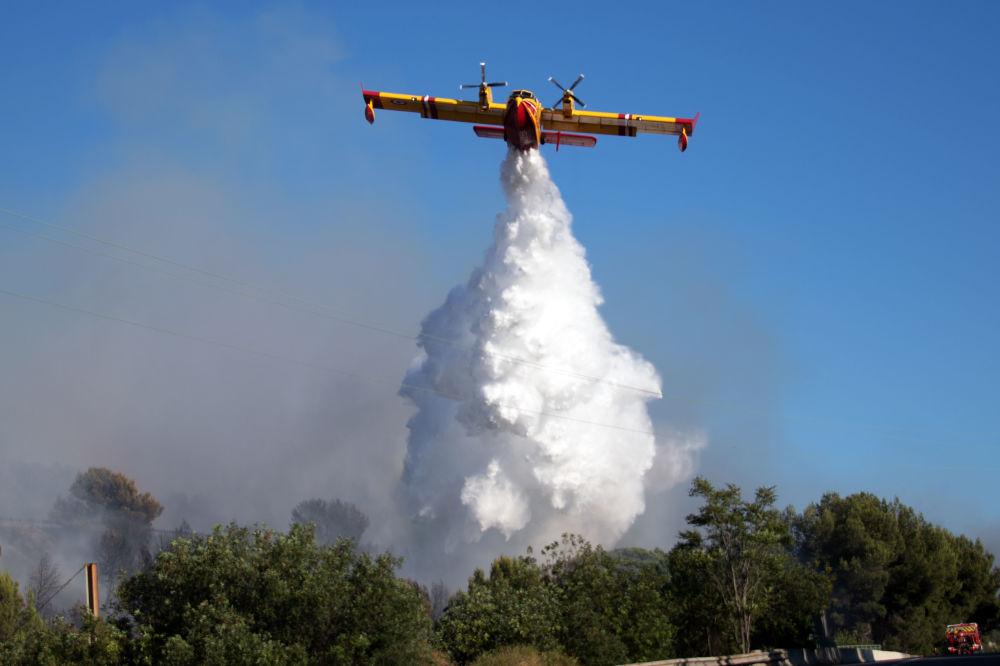 Aeronave de combate a incêndios descarrega água em um fogo perto da cidade de Vitrolles (França)