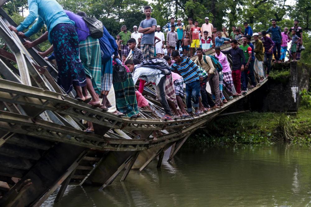 Transeuntes atravessando uma ponte danificada na cidade de Sylhet, Bangladesh