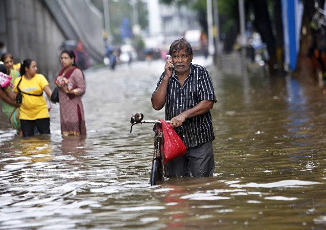 Um homem fala ao celular enquanto caminha em uma rua inundada devido às fortes chuvas em Mumbai, na Índia.