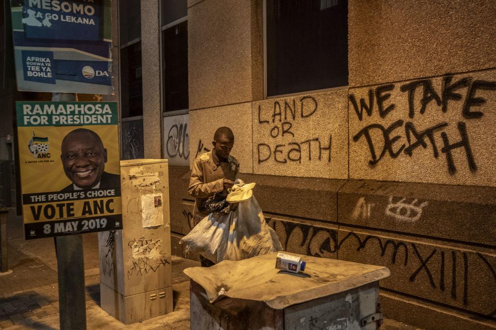 Homem passa diante de pôsteres de partidos pouco tempo antes das eleições em Joanesburgo, na África do Sul