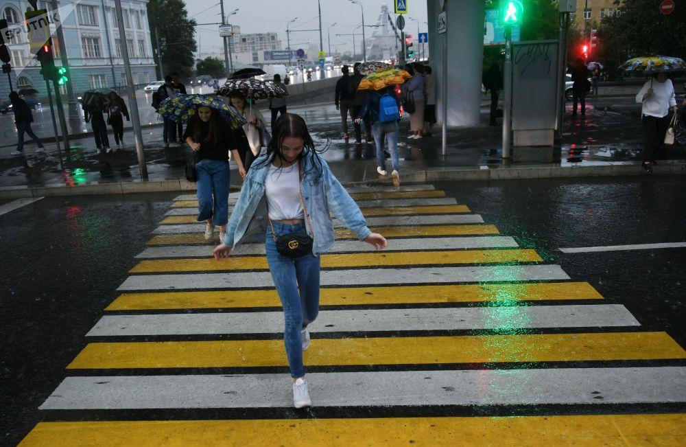 Jovem atravessando na faixa de pedestre com chuva, em Moscou