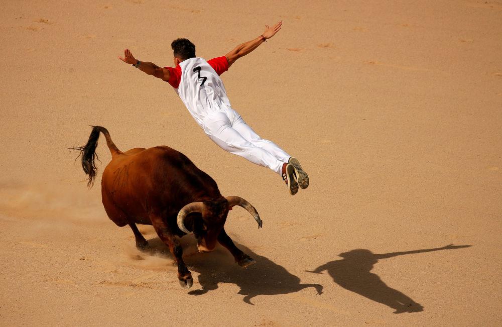 Recortador salta sobre o touro durante o Festival de São Firmino em Espanha