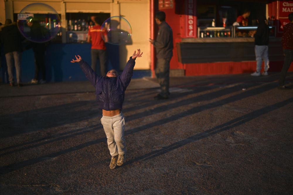 Menina apanhando bolhas de sabão em um parque de diversões em Montevideo, Uruguai
