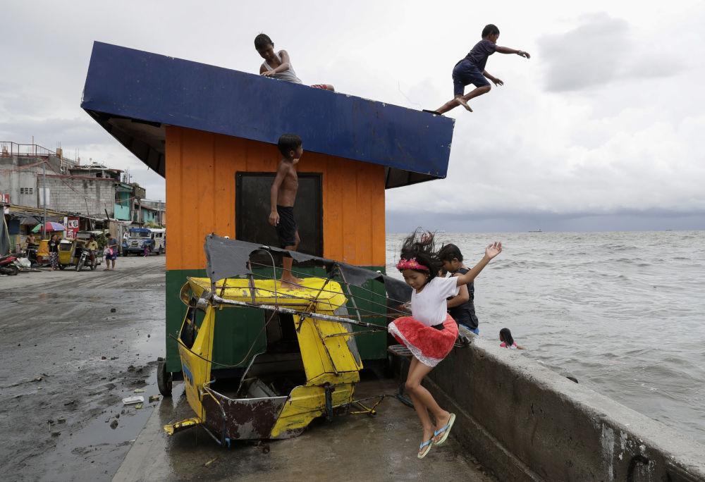 Crianças saltando na água em Manila, nas Filipinas