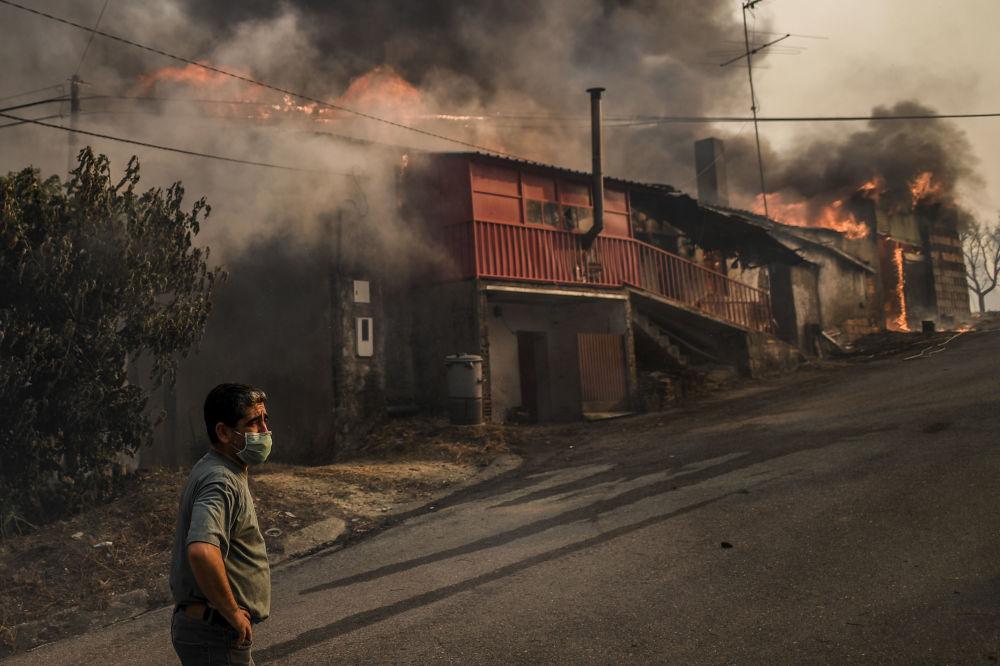 Morador usando máscara em frente a casa em chamas na aldeia de Roda, no centro de Portugal, em 21 de julho de 2019