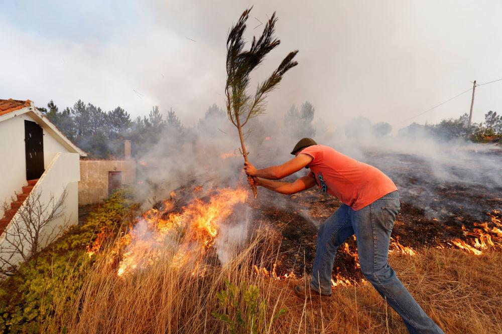 Moradores locais ajudam a apagar o incêndio florestal na aldeia de Colos, em Portugal, 21 de julho de 2019