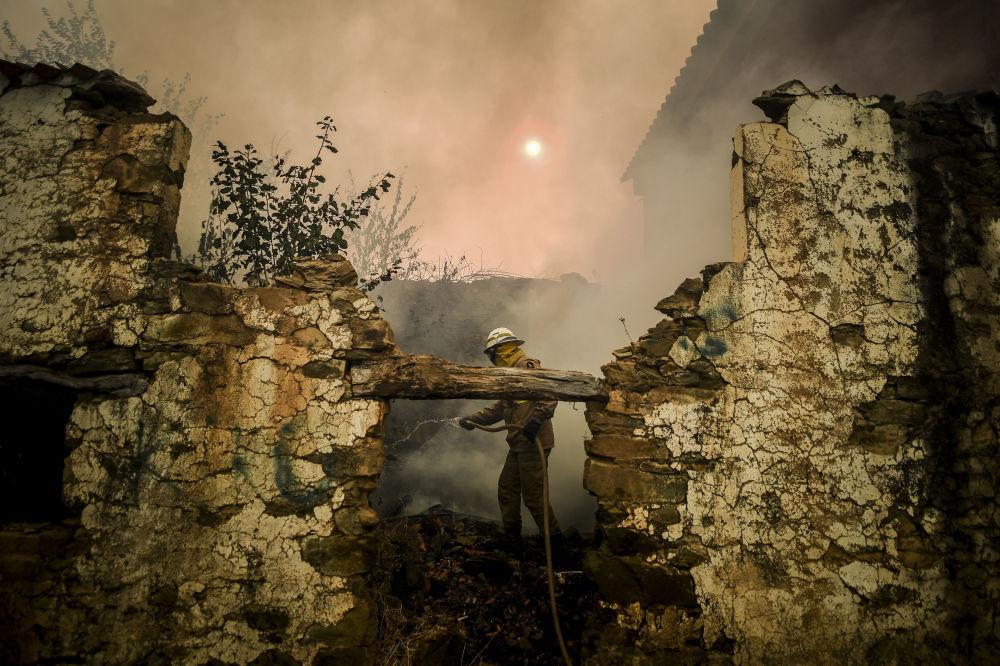 Bombeiro da Guarda Nacional usa mangueira durante incêndio na aldeia de Roda, no centro de Portugal, em 21 de julho de 2019